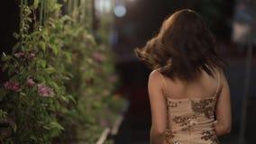 Bello sguardo della donna indietro alla macchina fotografica ed andare via nella città di notte, movimento lento video d archivio