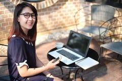 Bello sguardo della donna lavoratrice alla macchina fotografica ed al sorriso, lapto del computer immagini stock libere da diritti