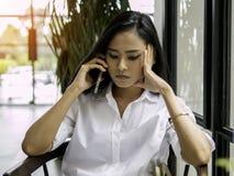 Bello smartphone asiatico della tenuta della donna di affari a disposizione e seriamente concentrato che ascolta una chiamata con fotografia stock libera da diritti