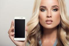Bello smartphone della tenuta della donna a disposizione Esposizione del modello Cl fotografia stock libera da diritti