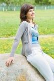Bello sogno della ragazza di seduta su una roccia immagine stock libera da diritti