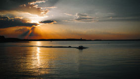 Bello sole dietro le nuvole, il mare e la barca Immagini Stock Libere da Diritti