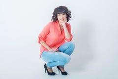 Bello sorridere alla moda della giovane donna, seduto davanti ad una parete bianca Fotografie Stock Libere da Diritti