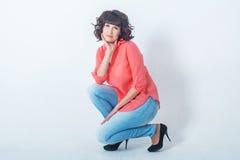 Bello sorridere alla moda della giovane donna, seduto davanti ad una parete bianca Immagini Stock
