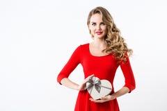 Bello sorridere in un vestito rosso con un contenitore di regalo sotto forma di un cuore Fotografia Stock Libera da Diritti