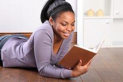 Bello sorriso dalla ragazza che legge un libro Fotografia Stock