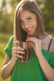 Bello sorriso di una ragazza che tiene un vetro di succo in sue mani Fotografia Stock