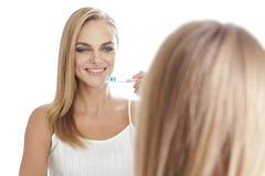 Bello spazzolino da denti biondo della tenuta della donna davanti ad uno specchio Fotografia Stock Libera da Diritti
