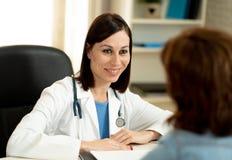 Bello specialista allegro di medico al suo ufficio dell'ospedale con dalla donna paziente del fuoco fotografia stock