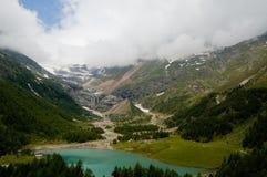 Bello stagno nelle montagne lungo la strada del treno rosso Immagini Stock Libere da Diritti