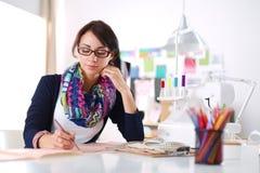 Bello stilista che si siede allo scrittorio in studio Fotografia Stock Libera da Diritti