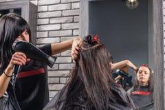 Bello stilista di capelli con le mani tatuate facendo uso di un fon sopra immagini stock libere da diritti