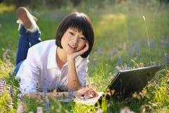 Bello studente asiatico che per mezzo del computer portatile all'aperto Fotografia Stock Libera da Diritti