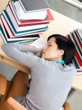 Bello studente che dorme allo scrittorio Fotografia Stock