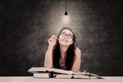 Bello studente che esamina lampadina accesa Immagine Stock