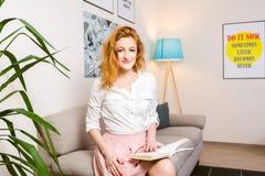 Bello studente della giovane donna con capelli rossi lunghi in libro di lettura rosa della camicia e della gonna, manuale disponi Fotografie Stock Libere da Diritti
