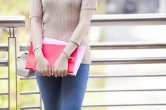 Bello studente di college femminile asiatico che tiene suo sorridere dei libri Fotografie Stock