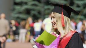 Bello studente di laurea felice che tiene mazzo di fiori, sorridente alla macchina fotografica archivi video