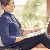 Bello studente felice con un computer portatile che si siede contro la finestra luminosa Fotografie Stock