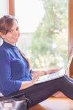 Bello studente felice con un computer portatile che si siede contro la finestra luminosa Fotografia Stock