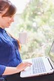 Bello studente felice con un computer portatile che si siede contro la finestra luminosa Immagini Stock