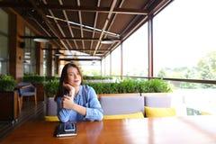 Bello studente femminile che si siede al caffè con lo smartphone ed il taccuino sulla tavola Fotografia Stock