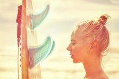 Bello surfista della ragazza con un bordo ad alba Vacanze estive in mare, stile di vita sano fotografia stock libera da diritti