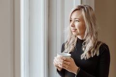 Bello tè bevente o caffè della giovane donna Fotografie Stock Libere da Diritti