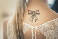 Bello tatoo dell'arco sul collo nuziale immagini stock