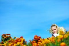 Bello teenager adulto fra i fiori gialli Fotografia Stock