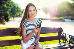 Bello telefono cellulare della tenuta della donna a disposizione e seduta sul banco Immagini Stock