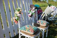 Bello terrazzo aperto nel giardino con le sedie bianche d'annata colorate tiffany, il cuscino variopinto del velluto e la palizza Immagini Stock
