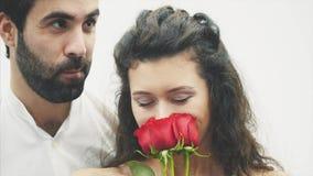 Bello tipo elegante in una camicia classica con le rose rosse in sue mani Compare su un fondo bianco Dà le rose a video d archivio