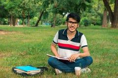 Bello tipo sorridente in vetri che si siedono sull'erba con i libri Fotografia Stock Libera da Diritti