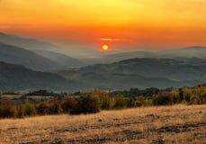 Bello tramonto arancio dietro le montagne Fotografia Stock