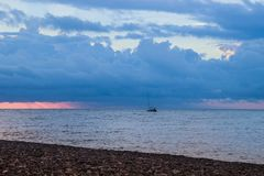 Bello tramonto con le nuvole luminose sopra il mare La costa è punteggiata con i ciottoli e una nave di navigazione immagini stock libere da diritti