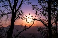 Bello tramonto del cielo con luce arancio sopra la natura variopinta fuori Immagine Stock