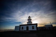 Bello tramonto dietro un faro bianco immagini stock libere da diritti