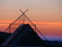 Bello tramonto dietro un tetto di una casa con la vista wounderful del paesaggio Immagini Stock
