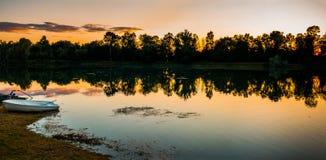 Bello tramonto dorato sopra il lago con la riflessione della foresta e una barca sola Immagini Stock Libere da Diritti