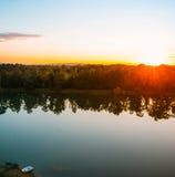 Bello tramonto dorato sopra il lago e una barca sola Fotografia Stock
