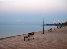Bello tramonto e banco sul lungonmare in Grecia fotografie stock