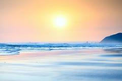 Bello tramonto giallo arancione sulla spiaggia dell'oceano. Immagine Stock