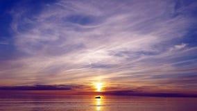 Bello tramonto multicolore sopra il mare la pietra si trova su un percorso soleggiato che riflette il tramonto nel mare Fotografia Stock Libera da Diritti