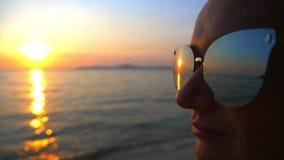 Bello tramonto soleggiato sul mare Vista tramite gli occhiali da sole la donna in occhiali da sole esamina il tramonto sul mare archivi video