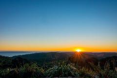 Bello tramonto sopra il golfo di Hauraki, con gli alberi e le colline profilati nella priorità alta Intrapreso la spiaggia a Fotografie Stock Libere da Diritti
