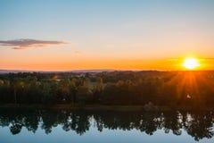 Bello tramonto sopra il lago con la riflessione della foresta in acqua Fotografie Stock