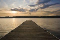 Bello tramonto sopra il paesaggio del lago con il molo Immagine Stock