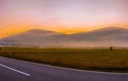 Bello tramonto sopra le montagne nebbiose Fotografia Stock