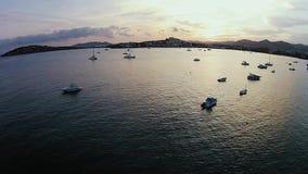 Bello tramonto su Ibiza, orizzonte nascosto dietro le montagne, le barche e la navigazione del galleggiamento degli yacht video d archivio